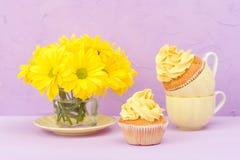 Пирожные украшенные с желтыми сливк и хризантемой на фиолетовой пастельной предпосылке для поздравительной открытки с текстовым у Стоковое Изображение