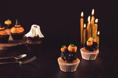 Пирожные хеллоуина и горящие свечи Стоковое Фото