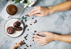 Пирожные шоколада с чашкой горячего черного кофе на предпосылке cocrete Женское пирожное отрезка рук Стоковые Изображения RF