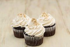 Пирожные шоколада с белыми замороженностью и золотом брызгают Стоковые Изображения