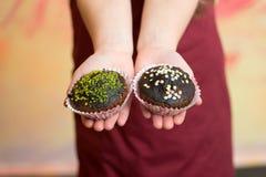 Пирожные шоколада с брызгают в руках малого младенца, ребенка Стоковые Фотографии RF