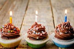 Пирожные шоколада с красочным брызгают с свечами Стоковое Изображение RF