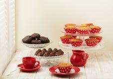 Пирожные, шоколады и кофе около окна с штарками Стоковая Фотография RF
