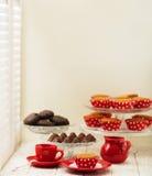 Пирожные, шоколады и кофе около окна с штарками Стоковое Изображение