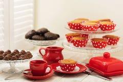 Пирожные, шоколады и кофе около окна с штарками Стоковые Изображения RF