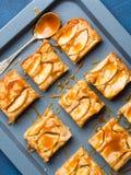 Пирожные Яблока белокурые с карамелькой на предпосылке сини подноса Стоковые Фото
