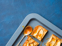 Пирожные Яблока белокурые с карамелькой на предпосылке сини подноса Стоковые Фотографии RF
