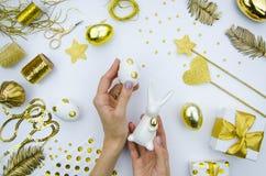 Пиршество святой пасхи Девушка держит зайчика пасхи фарфора и пасхальное яйцо белизны украшенными с золотыми кругами Стоковое Фото