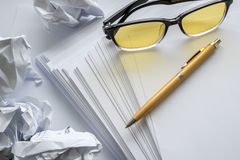 Писатель в мысли, скомканная бумага с ручкой и стекла Стоковые Изображения