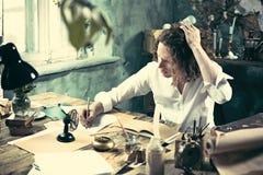 Писатель на работе Красивый молодой писатель сидя на таблице и писать что-то в его sketchpad стоковое фото
