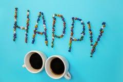 Писем слов взгляд сверху 2 предпосылки эспрессо кофе чашки шоколада камешков белизна керамических ярких голубых счастливая Стоковые Фотографии RF