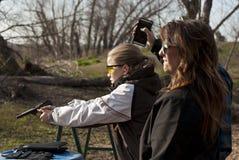 Пистолет стрельбы девочка-подростка с латунным летанием Стоковая Фотография