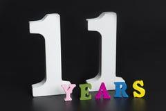 Письма и 11 лет на черной предпосылке Стоковые Изображения