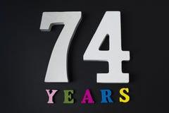 Письма и 74 лет на черной предпосылке Стоковое Изображение