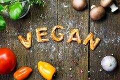 Письма и овощи теста на деревенском деревянном столе, vegan слова стоковое фото