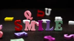 Письма улыбки пестротканые на черноте Стоковые Фото