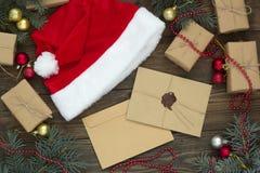 2 письма, шляпа santa среди подарков и рождество Стоковое Изображение