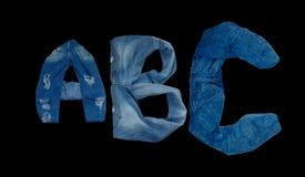 Письма ABC показывают что алфавит клал вне джинсы на черную предпосылку стоковая фотография