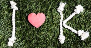 Письма i и k и 3 бумажных выхода отрезка сердца на траве Стоковая Фотография