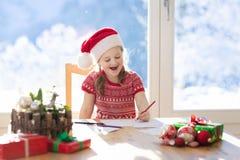 Письмо сочинительства ребенка к Санта на Рожденственской ночи Дети пишут Xmas присутствующую маленькую девочку списка целей сидя  стоковое фото