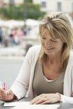 Письмо сочинительства женщины на кафе Outdoors Стоковая Фотография RF