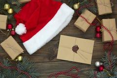 Письмо, шляпа santa среди подарков и рождество Стоковые Фото