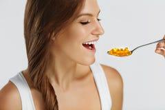 питание витамины еда здоровая Женщина есть пилюльки с Fis Стоковая Фотография