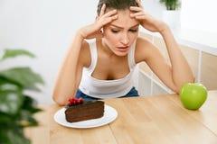 питание диетпитания Женщина выбирая между тортом и Яблоком стоковые изображения