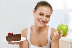 питание диетпитания Женщина выбирая между тортом и Яблоком стоковое фото