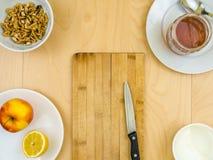 Питательные здоровые ингридиенты вокруг доски с ножом, яблоком, сыром, грецкими орехами и медом Стоковая Фотография