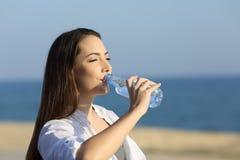 Питьевая вода дамы от бутылки на пляже Стоковое Изображение RF