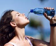 Питьевая вода женщины от бутылки после разминки спорта идущей снаружи стоковая фотография