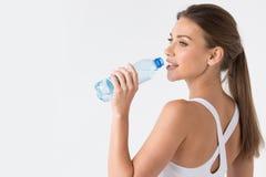 Питьевая вода женщины от голубой бутылки Стоковые Фотографии RF