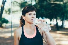 Питьевая вода женщины после тренировки в парке Стоковая Фотография RF