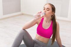 Питьевая вода женщины фитнеса на спортзале на белой предпосылке Стоковое Изображение