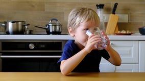 Питьевая вода мальчика на кухне видеоматериал
