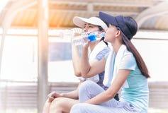 питьевая вода молодой женщины после законченный jogging на u Стоковые Изображения