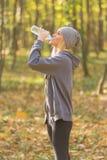Питьевая вода спортсменки во время jogging стоковые изображения rf