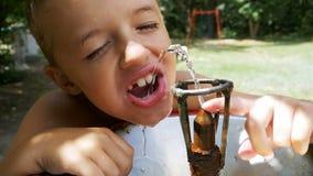 Питьевая вода счастливого мальчика смешная от выпивая фонтана на спортивной площадке в замедленном движении