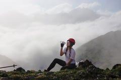 Питьевая вода hiker девушки на горе Стоковые Фото