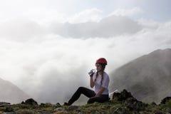 Питьевая вода hiker девушки на горе Стоковые Изображения