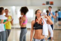 Питьевая вода брюнет в классе фитнеса после тренировки стоковая фотография rf