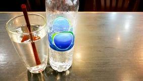 Питьевая вода бутылки и стекло воды с коричневой соломой Стоковая Фотография RF