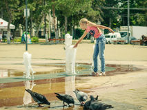 Питьевая вода голубей от общественного фонтана около развлекать девушки Стоковая Фотография