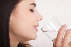 Питьевая вода девушки дома Стекло воды в утре перед завтраком Стоковые Фото