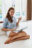 Питьевая вода женщины, используя компьютер, работая домой питье Связь Стоковые Фото