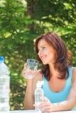 Питьевая вода женщины на пикнике Стоковые Фотографии RF