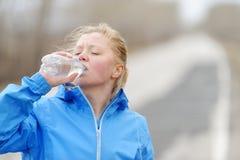 Питьевая вода женщины пригодности после хода пляжа Стоковое фото RF