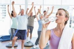 Питьевая вода женщины при люди протягивая руки на студии фитнеса Стоковая Фотография