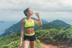 Питьевая вода женщины фитнеса от бутылки ослабляя после разработки слушать к музыке стоя на травянистой горе внутри Стоковая Фотография RF